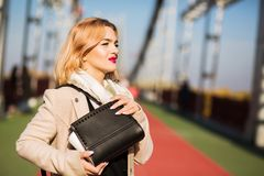Fashion portrait of attractive model wears beige coat , holding. Fashion portrait of attractive woman wears beige coat , holding black purse, posing at the Royalty Free Stock Images