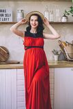 Fashion portrait of attractive stylish pregnant lady in long red sarafan and straw hat, photo of the happy and beautiful royalty free stock photos