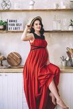 Fashion portrait of attractive stylish pregnant lady in long red sarafan and straw hat, photo of the happy and beautiful. Pregnant woman, becoming parrents royalty free stock photos