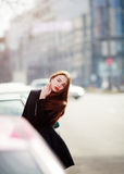 Fashion portrait of beautiful alluring young woman posing on a busy street among cars. Stock Photo