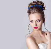 Fashion portrait of a beautiful attractive girl with a gentle elegant evening wedding hairstyles high and bright make-up with flow Stock Photos