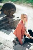 Fashion portrait of beautiful blond woman sitting on old stairs. In sunlight Stock Photo