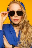 Fashion portrait of a beautiful blonde in a blue scarf and jacke Royalty Free Stock Photo