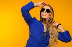 Fashion portrait of a beautiful blonde in a blue scarf and jacke Stock Image