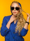 Fashion portrait of a beautiful blonde in a blue scarf and jacke Royalty Free Stock Images