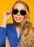 Fashion portrait of a beautiful blonde in a blue scarf and jacke Stock Photo