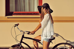 Fashion portrait of beautiful blonde on a vintage bicycle Stock Image