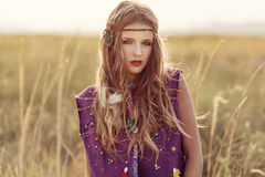 Fashion portrait of beautiful boho woman in the sunset field loo. King at camera Stock Images