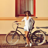 Fashion portrait of beautiful female model on a vintage bike Royalty Free Stock Photography
