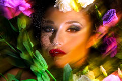 Fashion portrait of beautiful girl with bright make up among eustomas. royalty free stock images