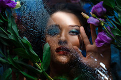 Fashion portrait of beautiful girl with bright make up among eustomas. Royalty Free Stock Photos