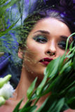 Fashion portrait of beautiful girl with bright make up among flowers. Stock Images