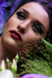Fashion portrait of beautiful girl with bright make up among flowers. Stock Photo