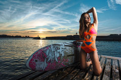 Fashion portrait: beautiful girl with surf board enjoing herself Stock Photos