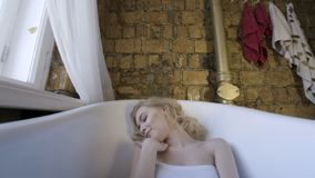 Fashion portrait of a beautiful girl wearing elegant bodysuit is lying in an empty bath and looking at a camera. Female stock photos
