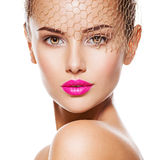 Fashion portrait of a beautiful  girl wears golden veil on face. Royalty Free Stock Image