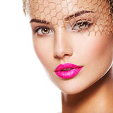 Fashion portrait of a beautiful girl wears golden veil on face. stock image