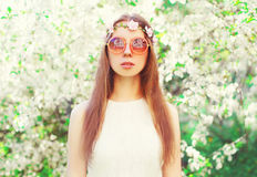 Fashion portrait beautiful hippie young woman over flowering. White garden background Stock Image
