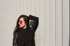 Fashion portrait of beautiful model with long hair in trendy coa. Fashion portrait of beautiful woman with long hair in trendy coat and stylish glasses posing at Stock Photo