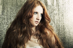 Fashion portrait beautiful redheaded woman. Fashion portrait of a young beautiful redheaded woman on a gold background stock photos