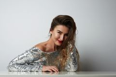 Fashion portrait of a beautiful smiling woman with long hair in a pretty silver dress with tinsel sitting at the table Royalty Free Stock Photo