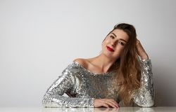 Fashion portrait of a beautiful smiling woman with long hair in a pretty silver dress with tinsel sitting at the table Royalty Free Stock Photos