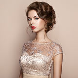 Fashion portrait of beautiful woman in elegant dress. Girl with elegant hairstyle and jewelry Royalty Free Stock Photography