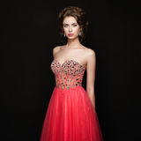 Fashion portrait of beautiful woman in elegant dress. Girl with elegant hairstyle and jewelry Royalty Free Stock Photo