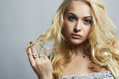 Fashion portrait of Beautiful woman.Flirt Blond Girl with Curly hair. Close-up fashion portrait of Beautiful woman.Flirt Blond Girl with Curly hair.Enjoy.Gray royalty free stock image