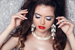 Fashion Portrait of beautiful woman with perfect make up over pa. Rty lights. Jewelry and Beauty Stock Images