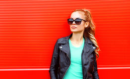Fashion portrait beautiful woman in sunglasses black rock jacket over red. Background Stock Photos