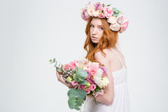 Fashion portrait of beautiful woman in wreath holding flowers bouquet Royalty Free Stock Photography