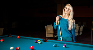 Fashion portrait of beautiful young blonde girl plays billiard Stock Photography