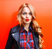 Fashion portrait beautiful young blonde woman blowing red lips making kiss wearing a black rock style over colorful. Background stock photos