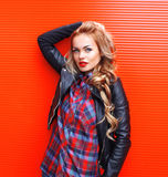 Fashion portrait beautiful young blonde woman with red lips wearing a black rock style over colorful Stock Image