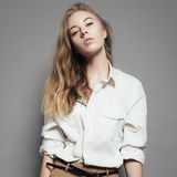 Fashion portrait of a beautiful young blonde woman in a white shirt in the studio on a gray background Stock Images