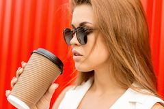 Business lady urban lifestyle. Fashion portrait of beautiful young business lady in white vogue suit with to go cup of hot tea or coffee against red wall. Urban royalty free stock image