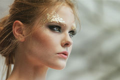 Fashion portrait of a beautiful young girl with fantasy golden m Stock Photography