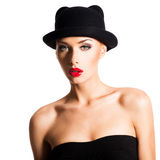 Fashion portrait of a beautiful young girl wearing a black hat. Stock Photos