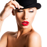 Fashion portrait of a beautiful young girl wearing a black hat. Royalty Free Stock Photos