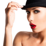 Fashion portrait of a beautiful young girl wearing a black hat. Stock Photography