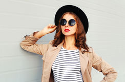 Fashion portrait beautiful young woman with red lips wearing black hat sunglasses coat over grey background. Fashion portrait beautiful young woman with red lips Royalty Free Stock Photography