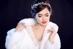 Fashion portrait of beautiful young woman in white fur coat with Stock Images