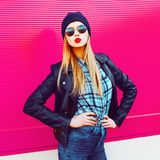 Fashion portrait blonde cool girl sending sweet air kiss posing in rock black style jacket, hat posing on city street. Over colorful pink wall background stock image
