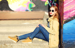 Fashion portrait blonde pretty young woman sitting in city. Over colorful background Royalty Free Stock Image