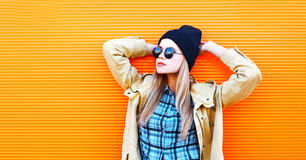 Fashion portrait blonde woman in black sunglasses and hat on a colorful orange background Royalty Free Stock Photography