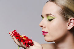 Fashion portrait of a blonde woman holding a flower Royalty Free Stock Photography