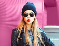 Fashion portrait blonde woman sending sweet air kiss in rock black style jacket, hat posing on city street over colorful pink wall. Background stock image