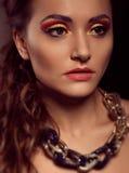 Fashion portrait of brown-eyes  woman.Gold jewelry. Orange yello Stock Photos