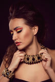 Fashion portrait of brown-eyes  woman.Gold jewelry. Orange yello Royalty Free Stock Photography